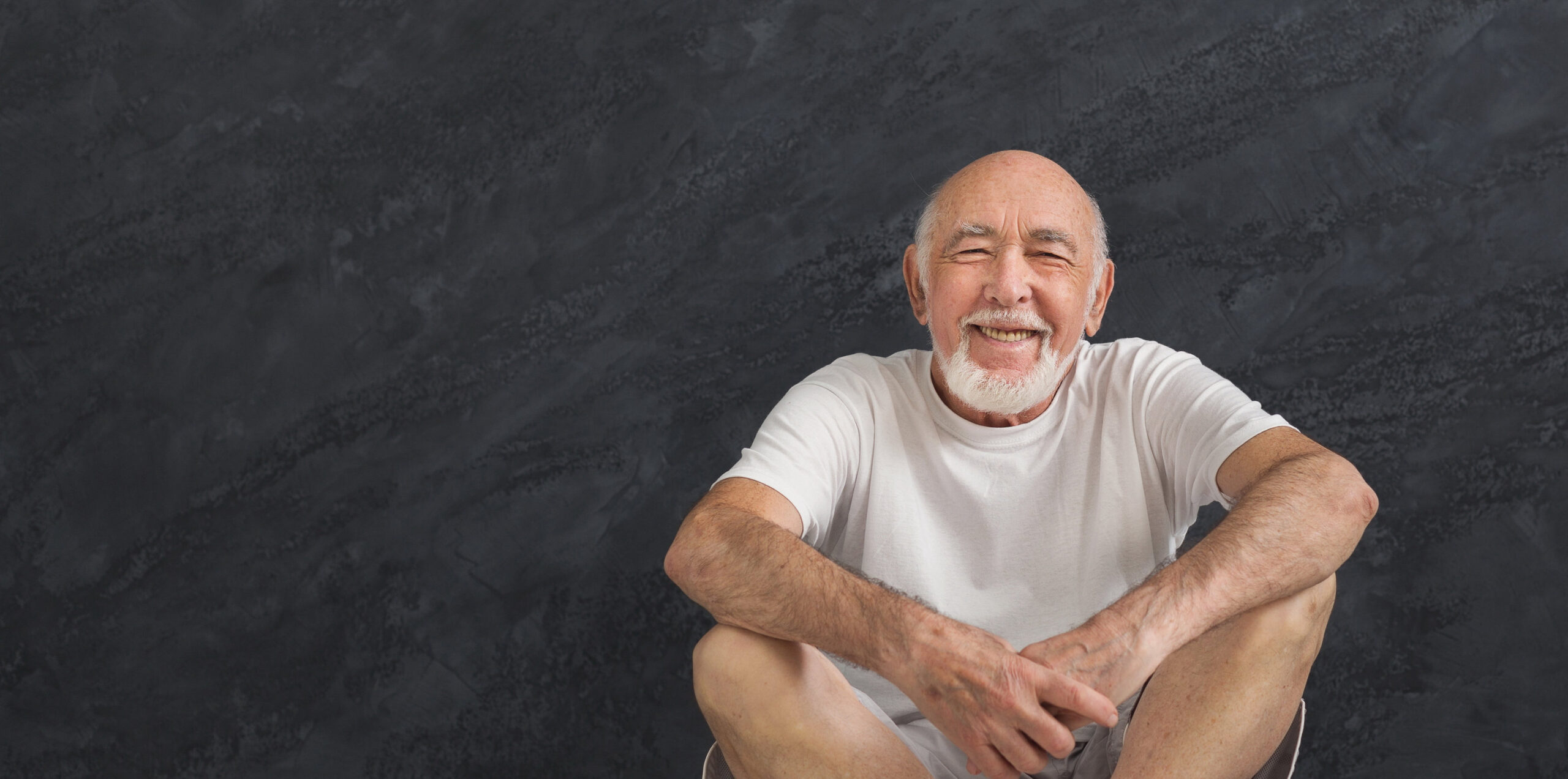Senior fitness man have rest. Cheerful sporty mature guy sitting in lotus pose after good training, black background. Active lifestyle and healthcare in any age, copy space