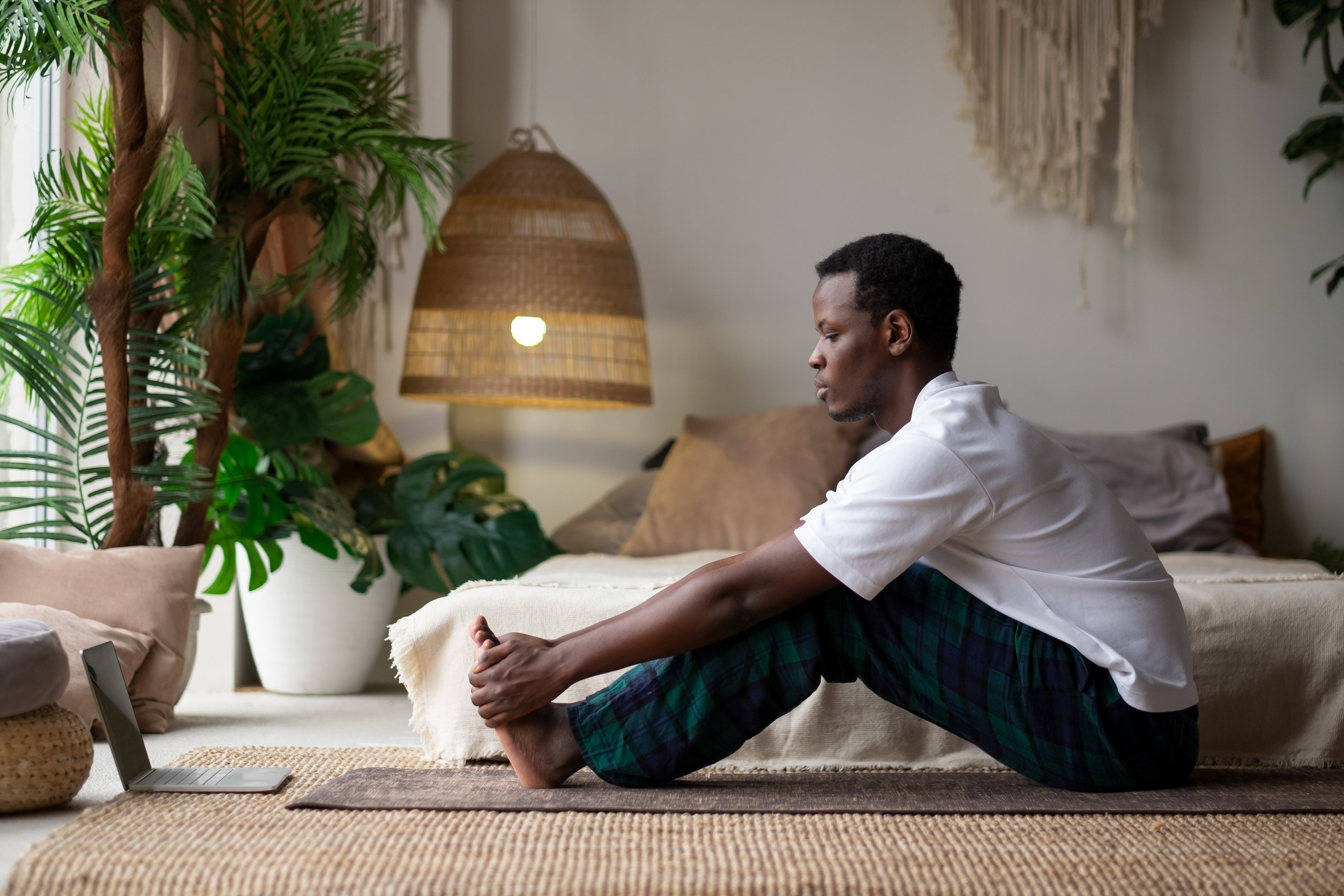 African young man sitting in paschimottanasana or Intense Dorsal Stretch pose, seated forward bend posture, exercise for hips and spine at home