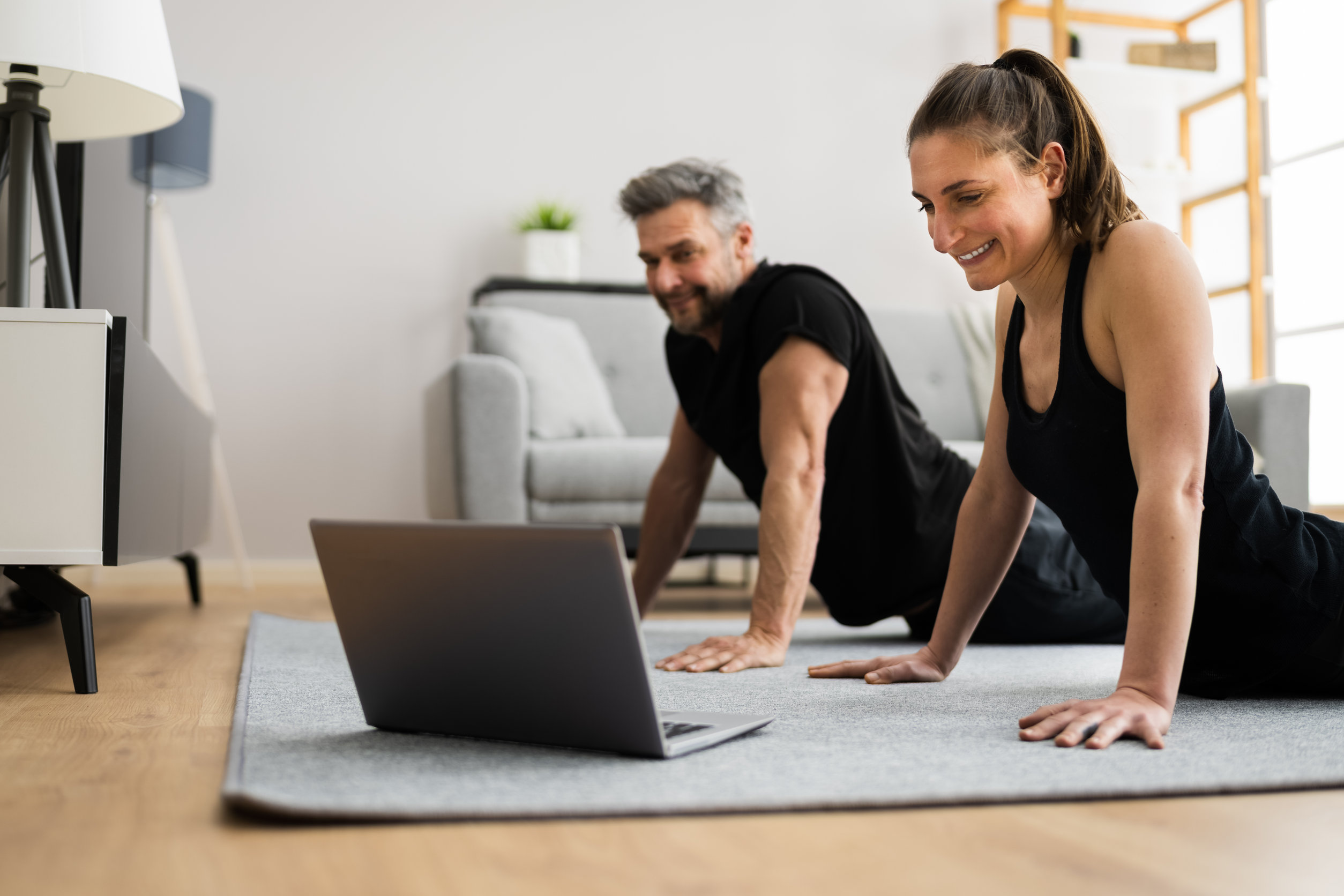 Couple Doing Online Stretching Class Workout And Fitness Exercise